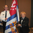 P/D/C Ken Danley and D/C Millie Steffe with D30's 100th anniversary Ensign